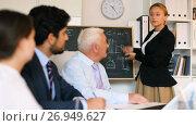Купить «Office manager female is reading financial report to colleagues on meeting in the office», видеоролик № 26949627, снято 5 июля 2017 г. (c) Яков Филимонов / Фотобанк Лори