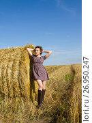 Купить «Девушка в резиновых сапогах и короткой юбке стоит у тюка соломы», фото № 26950247, снято 16 сентября 2017 г. (c) Момотюк Сергей / Фотобанк Лори