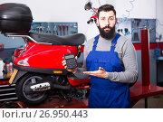 Купить «Hard-working concluded the cost of repairing the scooter», фото № 26950443, снято 19 августа 2018 г. (c) Яков Филимонов / Фотобанк Лори
