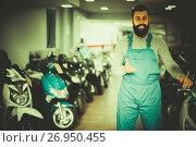 Купить «Smiling male worker demonstrating motorcycles», фото № 26950455, снято 21 сентября 2019 г. (c) Яков Филимонов / Фотобанк Лори