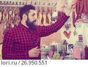 Купить «Young male customer examining sausages in butcher's shop», фото № 26950551, снято 16 ноября 2016 г. (c) Яков Филимонов / Фотобанк Лори