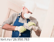 Купить «Adult male builder renovating with drill in mask», фото № 26950783, снято 18 мая 2017 г. (c) Яков Филимонов / Фотобанк Лори