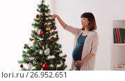 Купить «pregnant woman decorating christmas tree at home», видеоролик № 26952651, снято 14 сентября 2017 г. (c) Syda Productions / Фотобанк Лори