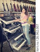 Купить «Girl choosing synthesizer in store», фото № 26962007, снято 19 августа 2018 г. (c) Яков Филимонов / Фотобанк Лори