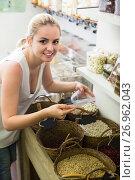 Купить «Happy female customer buying dried beans», фото № 26962043, снято 15 ноября 2018 г. (c) Яков Филимонов / Фотобанк Лори