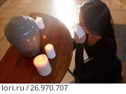 Купить «woman with cremation urn at funeral in church», фото № 26970707, снято 20 марта 2017 г. (c) Syda Productions / Фотобанк Лори