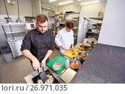 Купить «chef and cook cooking food at restaurant kitchen», фото № 26971035, снято 2 апреля 2017 г. (c) Syda Productions / Фотобанк Лори