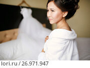 A bride in a white robe from the morning before putting on a wedding dress on a wedding day. Стоковое фото, фотограф Евгений Майнагашев / Фотобанк Лори
