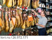 Купить «Elderly man selecting Spanish jamon leg», фото № 26972171, снято 5 октября 2016 г. (c) Яков Филимонов / Фотобанк Лори