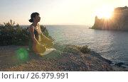 Купить «Woman meditates against the sea», видеоролик № 26979991, снято 19 сентября 2017 г. (c) Илья Шаматура / Фотобанк Лори
