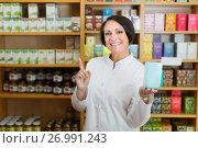 Купить «Woman seller in uniform holding dietary supplement in box», фото № 26991243, снято 15 декабря 2018 г. (c) Яков Филимонов / Фотобанк Лори