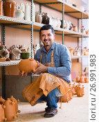 Купить «cheerful man potter holding ceramic vessels», фото № 26991983, снято 20 октября 2018 г. (c) Яков Филимонов / Фотобанк Лори