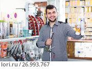 Купить «positive male customer examining various glue tubes in store», фото № 26993767, снято 5 апреля 2017 г. (c) Яков Филимонов / Фотобанк Лори