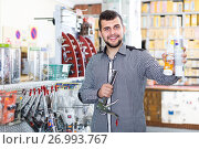 positive male customer examining various glue tubes in store. Стоковое фото, фотограф Яков Филимонов / Фотобанк Лори
