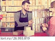 Купить «Seller assisting woman in choosing door hinges», фото № 26993819, снято 5 апреля 2017 г. (c) Яков Филимонов / Фотобанк Лори