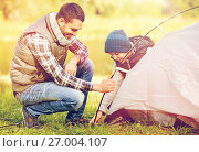 happy father and son setting up tent outdoors. Стоковое фото, фотограф Syda Productions / Фотобанк Лори