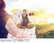 Купить «happy couple with picnic blanket at campsite», фото № 27004111, снято 27 сентября 2015 г. (c) Syda Productions / Фотобанк Лори