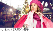 Купить «happy woman with shopping bags over christmas fair», фото № 27004499, снято 10 октября 2010 г. (c) Syda Productions / Фотобанк Лори