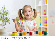 Купить «Cute child girl painting picture on home interior background», фото № 27009947, снято 30 сентября 2015 г. (c) Оксана Кузьмина / Фотобанк Лори