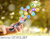 hand with phone with application icons coming up from it. Green boke background. Стоковое фото, агентство Wavebreak Media / Фотобанк Лори