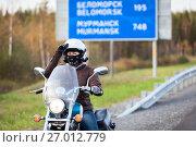 Купить «Девушка мотоциклист на фоне дорожного указателя расстояний», фото № 27012779, снято 24 сентября 2017 г. (c) Кекяляйнен Андрей / Фотобанк Лори