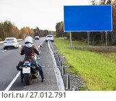 Купить «Женщина мотоциклист смотрит на пустой информационный указатель, стоя на обочине дороги на мотоцикле», фото № 27012791, снято 24 сентября 2017 г. (c) Кекяляйнен Андрей / Фотобанк Лори