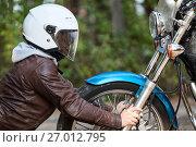 Купить «Мотоциклист в шлеме смотрит на фару мотоцикла», фото № 27012795, снято 24 сентября 2017 г. (c) Кекяляйнен Андрей / Фотобанк Лори