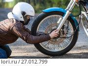 Купить «Мотоциклист проверяет колесо мотоцикла», фото № 27012799, снято 24 сентября 2017 г. (c) Кекяляйнен Андрей / Фотобанк Лори