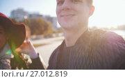 Купить «Young man and her wife making selfie at sunset outdoor», видеоролик № 27012819, снято 14 декабря 2018 г. (c) Константин Шишкин / Фотобанк Лори