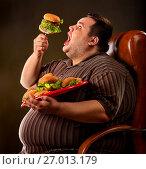 Купить «Fat man eating fast food hamberger. Breakfast for overweight person.», фото № 27013179, снято 24 марта 2017 г. (c) Gennadiy Poznyakov / Фотобанк Лори