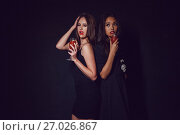 Купить «Attractive girls in the image of vampires hold glasses with blood. Halloween.», фото № 27026867, снято 22 сентября 2017 г. (c) Женя Канашкин / Фотобанк Лори