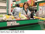 Купить «Кассир на кассе супермаркета Окей за работой», фото № 27027415, снято 30 сентября 2017 г. (c) Юлия Юриева / Фотобанк Лори