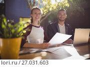 Купить «Portrait of smiling young creative professionals sitting with laptop at coffee shop», фото № 27031603, снято 21 мая 2017 г. (c) Wavebreak Media / Фотобанк Лори