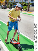 Купить «Florida, Miami Beach, Ocean Drive, bicycle lane, electric scooter, man, senior, pushing, riding», фото № 27032867, снято 9 апреля 2017 г. (c) age Fotostock / Фотобанк Лори