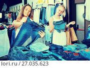 Купить «Two positive girls choosing denim trousers», фото № 27035623, снято 23 октября 2018 г. (c) Яков Филимонов / Фотобанк Лори