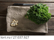 Купить «Fresh kale leaves with garlic on napkin at table», фото № 27037927, снято 12 июня 2017 г. (c) Wavebreak Media / Фотобанк Лори