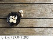 Купить «Garlics in plate on wooden table», фото № 27047203, снято 5 июня 2017 г. (c) Wavebreak Media / Фотобанк Лори