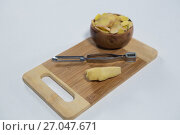 High angle view of fresh finger with peeler and bowl on wooden serving board. Стоковое фото, агентство Wavebreak Media / Фотобанк Лори