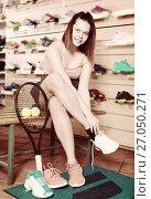 Girl trying sneakers in sport store. Стоковое фото, фотограф Яков Филимонов / Фотобанк Лори