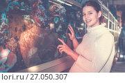 Купить «Girl in aquarium shop with interest looking at colorful fishes», фото № 27050307, снято 17 февраля 2017 г. (c) Яков Филимонов / Фотобанк Лори