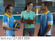 Coach talking with volleyball players at court. Стоковое фото, агентство Wavebreak Media / Фотобанк Лори