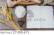 Купить «Book, eggs, flour, cookie cutter and wheat stem kept on a table 4k», видеоролик № 27055671, снято 22 ноября 2017 г. (c) Wavebreak Media / Фотобанк Лори