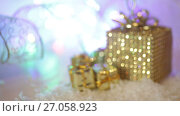 Купить «Golden gift boxes with snow and ribbon. Decoration for Christmas winter holidays, present with abstract bokeh shiny glowing blur lights background», видеоролик № 27058923, снято 5 октября 2017 г. (c) Happy Letters / Фотобанк Лори