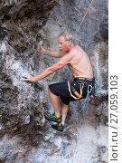 Купить «Мужчина скалолаз с голым торсом начинает восхождение по отвесной горной стене», фото № 27059103, снято 15 декабря 2010 г. (c) Эдуард Паравян / Фотобанк Лори
