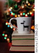 Купить «Christmas celebration with cup and gift box on books over bokeh and trees background», фото № 27060215, снято 12 мая 2017 г. (c) Tetiana Chugunova / Фотобанк Лори