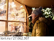 Купить «happy man looking at christmas market shop window», фото № 27062307, снято 2 декабря 2016 г. (c) Syda Productions / Фотобанк Лори