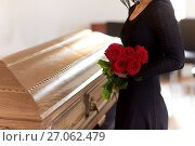 woman with red roses and coffin at funeral. Стоковое фото, фотограф Syda Productions / Фотобанк Лори