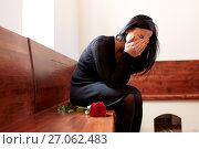Купить «crying woman with red rose at funeral in church», фото № 27062483, снято 20 марта 2017 г. (c) Syda Productions / Фотобанк Лори