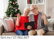 Купить «happy senior couple with tablet pc at christmas», фото № 27062607, снято 14 сентября 2017 г. (c) Syda Productions / Фотобанк Лори