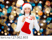 Купить «woman in santa hat with christmas gift and sock», фото № 27062803, снято 15 августа 2013 г. (c) Syda Productions / Фотобанк Лори